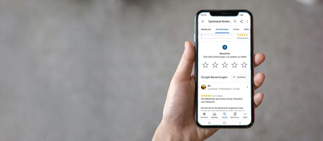 Smartphone mit Google Bewertung in der Hand